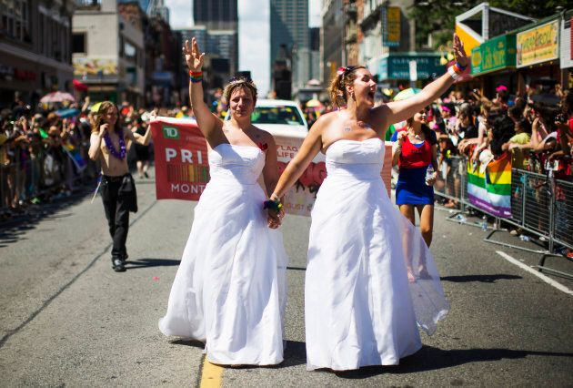 A newly wed lesbian couple marching in wedding dresses at the Toronto gay pride parade in Toronto, June...