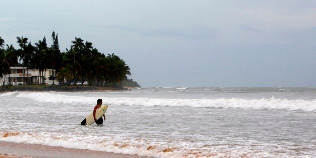A surfer walks into the ocean in the waters of La Pared Beach in the aftermath of Hurricane Irma in Luquillo,...