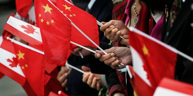 People gather holding Chinese and Canadian flags in Vancouver,