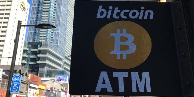 A sign is seen outside a business where a Bitcoin ATM is located in Toronto, Ont., June 3,