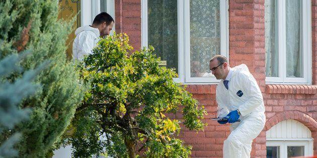 Police forensic investigators enter a home in Saint-Eustache, Que. on Sept.15, 2017. Quebec provincial...