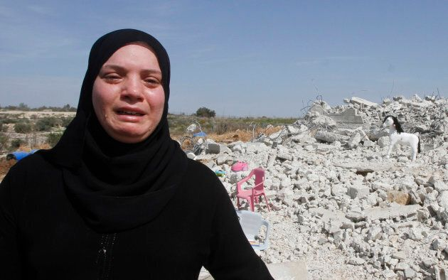 Palestinian woman Taghreed Sholi cries near the rubble of her house, which was demolished by the Israeli...