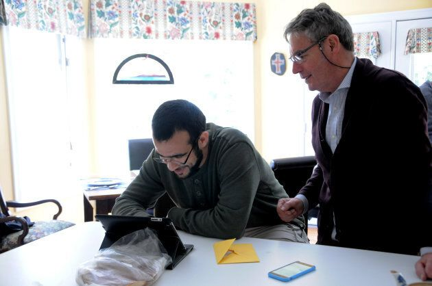 Omar Khadr uses a tablet alongside his longtime Canadian lawyer Dennis Edney on May 9,