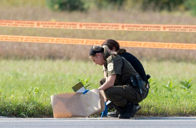 Quebec provincial police officers check a for evidence in Lachute, Que. on Sept. 15 ,