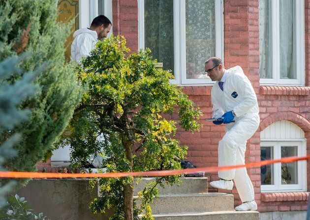Police forensic investigators enter a home in Saint-Eustache, Que. on Sept. 15,