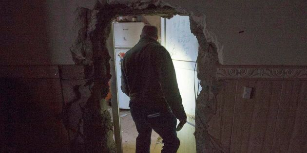 A reporter walks through a passageway opened by ISIS fighters to connect adjoining houses on Feb. 23,...