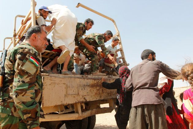 Sunni Muslims who fled the Islamic State's strongholds of Hawija and Shirqat arrive at the town of Dibis,...