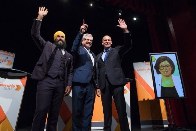 Left to right: Jagmeet Singh, Charlie Angus and Guy Caron pose for a photo, as Niki Ashton is seen on a television screen via satellite from Ottawa, before a federal NDP leadership debate in Vancouver on Sept. 10, 2017.