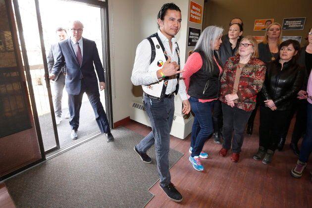 Wab Kinew enters a room with former premier Greg Selinger in Winnipeg on March 11,