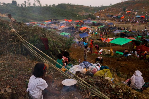 Rohingya girl prepare food in the side of her makeshift tent at the Thenkhali refugee camp in Coxs Bazar,...