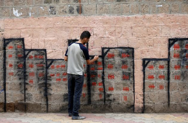 Artist and activist Thiyazen al-Alawi paints a mural on a wall of a hospital as part of a cholera awareness...