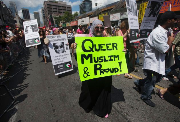 "A woman carrying a sign that reads, ""Queer, Muslim and Proud"" marches during the Gay Pride parade in Toronto July 1, 2012."