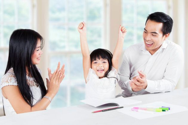 Image of a little girl finishing homework and get applause from her parents at home
