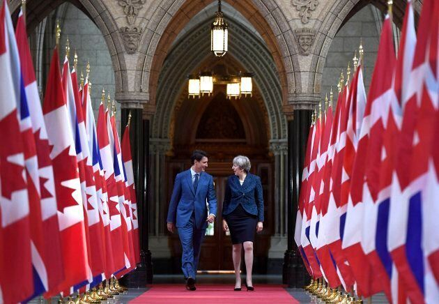 Prime Minister Justin Trudeau and British Prime Minister Theresa May walk in the Hall of Honour on Parliament...
