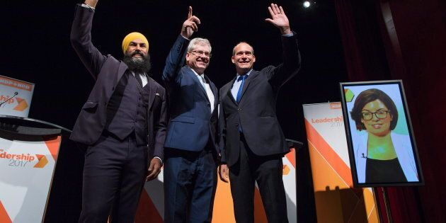 Jagmeet Singh, Charlie Angus and Guy Caron pose for a photograph as Niki Ashton is seen on a television screen via satellite from Ottawa before the NDP leadership debate in Vancouver on Sept. 1, 2017.