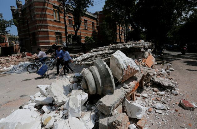 People walk next to debris after an earthquake in Mexico City on