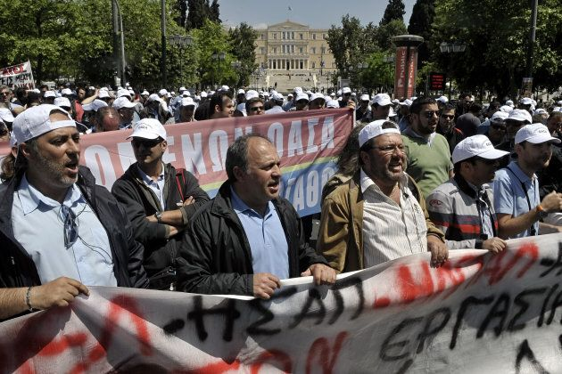 Public transport employees on strike shout slogans and walk behind a banner as they demonstrate outside the Greek Finance ministry  in Athens on April 27, 2010,  to protest against government's austerity measures.