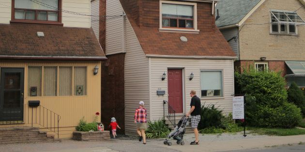 A family passes a house for sale listed at a price of $999,000 on Mount Pleasant Road in Toronto, Aug....