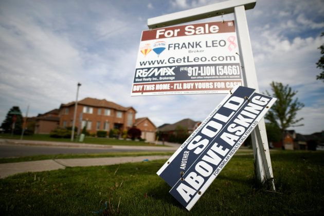 A real estate sign stands in front of housing in Vaughan, a suburb in Toronto, May 24,