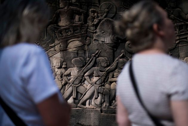 Tourists enjoy the figures carved on stone at Angkor Thom on Jan. 2, 2016 in Siem Riep, Cambodia. Angkor...