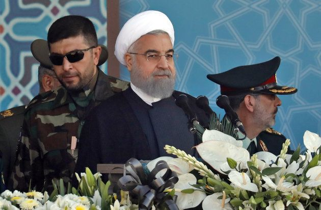Iranian President Hassan Rouhani sits among senior army staff as he delivers his speech during the annual...