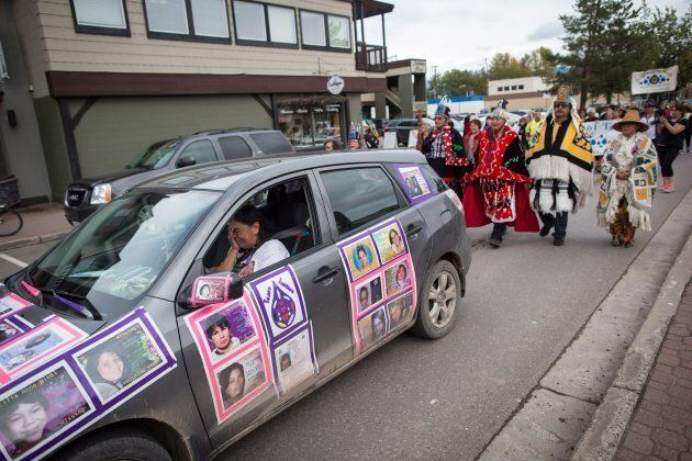 Driving a car covered with photos of missing women, Gladys Radek, is overcome with emotion as she leads...