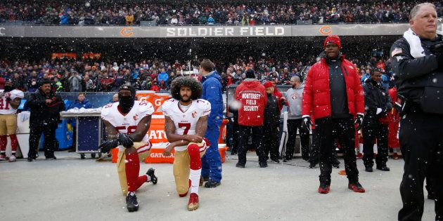 Eli Harold (58) and Colin Kaepernick (7) of the San Francisco 49ers kneel on the sideline, during the...