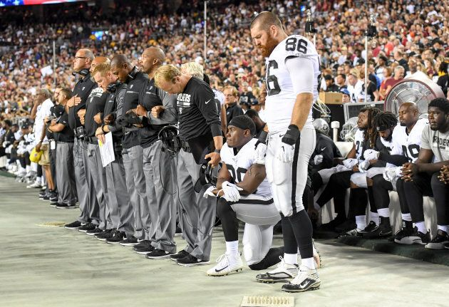Oakland Raiders running back Jalen Richard (30) takes a knee as his coaching staff and tight end Lee Smith (86) stand while others sit on the bench during the national anthem prior to action against the Washington Redskins at FedEx Field.