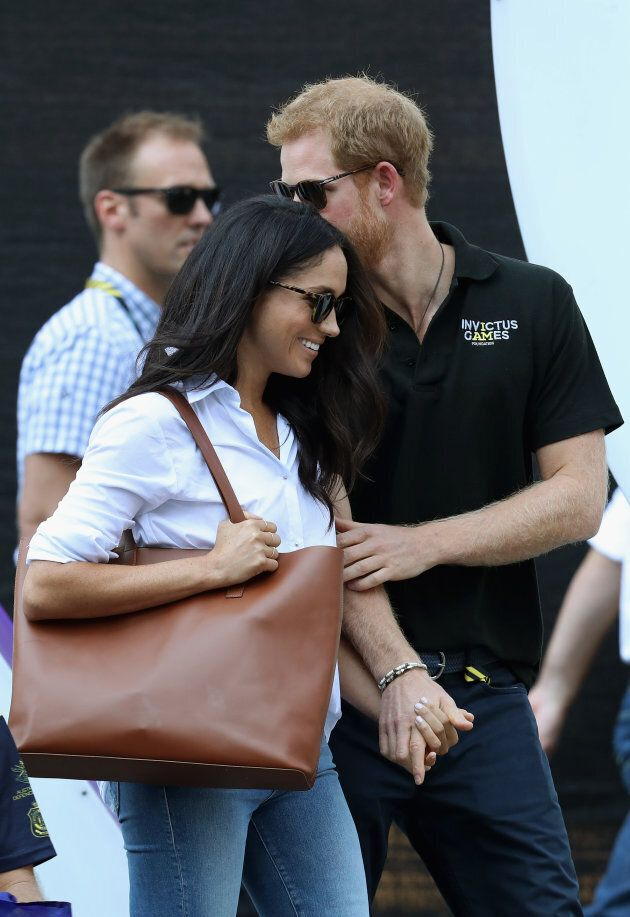 Prince Harry and Meghan Markle hold hands at a wheelchair tennis match during the Invictus Games 2017...