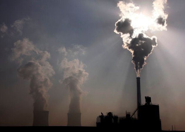 A coal-burning power plant can be seen behind a factory in the city of Baotou, in China's Inner Mongolia...
