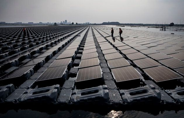Chinese workers walk on a section of a large floating solar farm project under construction by the Sungrow...
