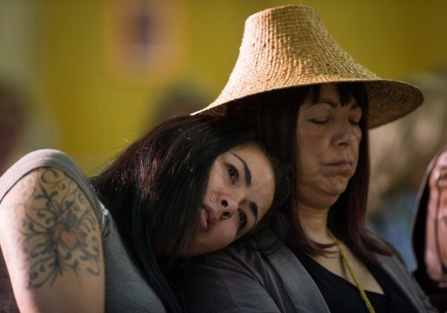 Megan Printz, left, rests her head on her mom Lorna Brown's shoulder while listening to Chief Vivian...