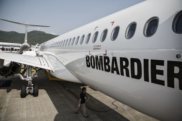 A technician walks under the belly of a Bombardier CS300 passenger jet.