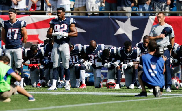 Members of the New England Patriots take a knee during the national anthem before a game against the...
