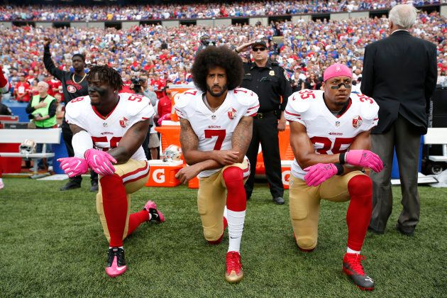 Eli Harold #58, Colin Kaepernick #7 and Eric Reid #35 of the San Francisco 49ers kneel in protest on...