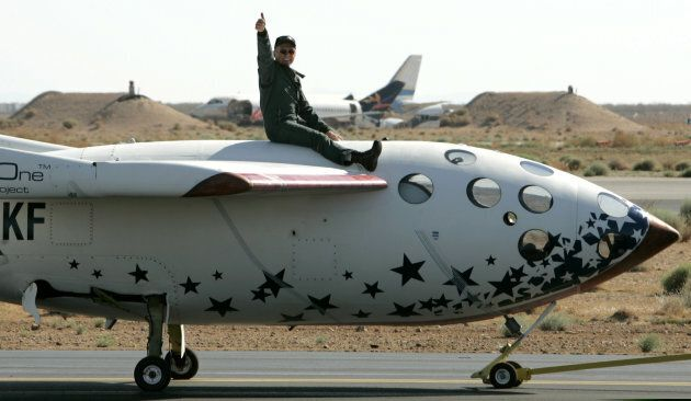 Pilot Mike Melville gives a thumbs up as he sits atop SpaceShipOne as it is towed following his historic flight of the world's first privately funded rocket plane beyond Earth's atmosphere at the Mojave Airport in California, U.S. on June 21, 2004.