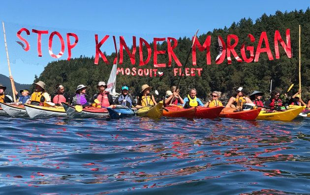 'Kayaktivists' hold up banner protesting plans by Kinder Morgan to build a pipeline during a water-based...