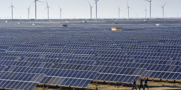 Workers walk past solar panels and wind turbines (rear) at a newly-built power plant in Hami, Xinjiang...