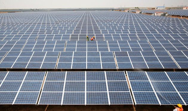 Workers install photovoltaic solar panels at the Gujarat solar park under construction in Charanka village...