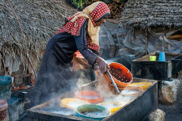 A woman prepares anchovies for drying at Mkokotoni village, Zanzibar, Tanzania.