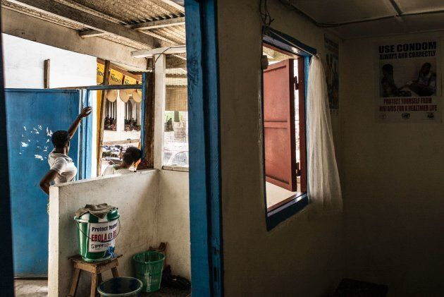 Women stand at the entrance of a clinic in Monrovia, Liberia, on May 2, 2016. Family planning services,...