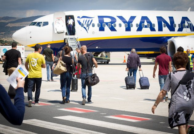 Passengers on the tarmac at Comiso Airport in Sicily, Italy walking with carry-on luggage toward a Ryanair airplane.