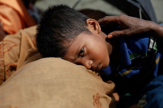 A boy is comforted as Rohingya refugees from Myanmar rest after arriving by a wooden boat to the shore...