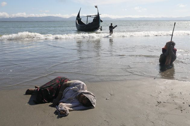 Women collapse from exhaustion as Rohingya refugees arrive by a wooden boat from Myanmar to the shore...