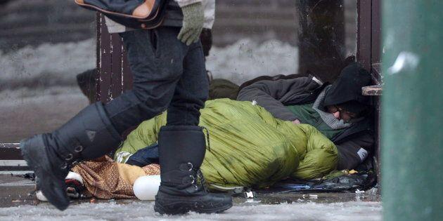 A homeless man sleeps in a doorway in Vancouver's Downtown Eastside, Dec. 19,