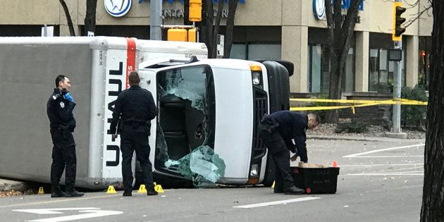 Edmonton police investigate the scene where a suspect hit pedestrians with a U-Haul truck, which then flipped at the intersection at 107 Street and 100 Avenue in front of the Matrix Hotel on Sunday.