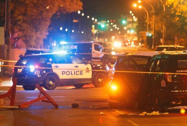 Police investigate the scene where a car crashed into a roadblock in Edmonton on