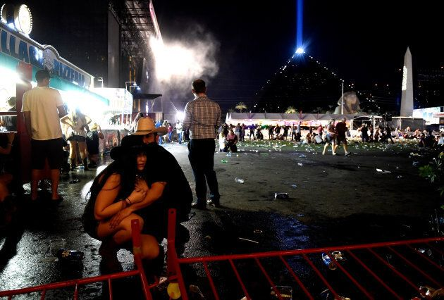 People take cover at the Route 91 Harvest country music festival after gun fire was heard on Sunday night in Las Vegas.
