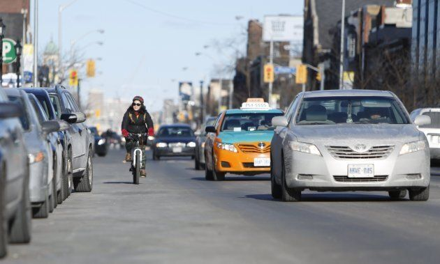 A cyclist going west with traffic on Danforth Avenue in Toronto on March 17,