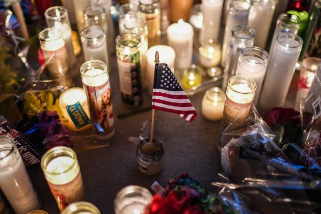 A U.S. flag is placed in the middle of flowers and candles at a vigil that was held for the victims along...